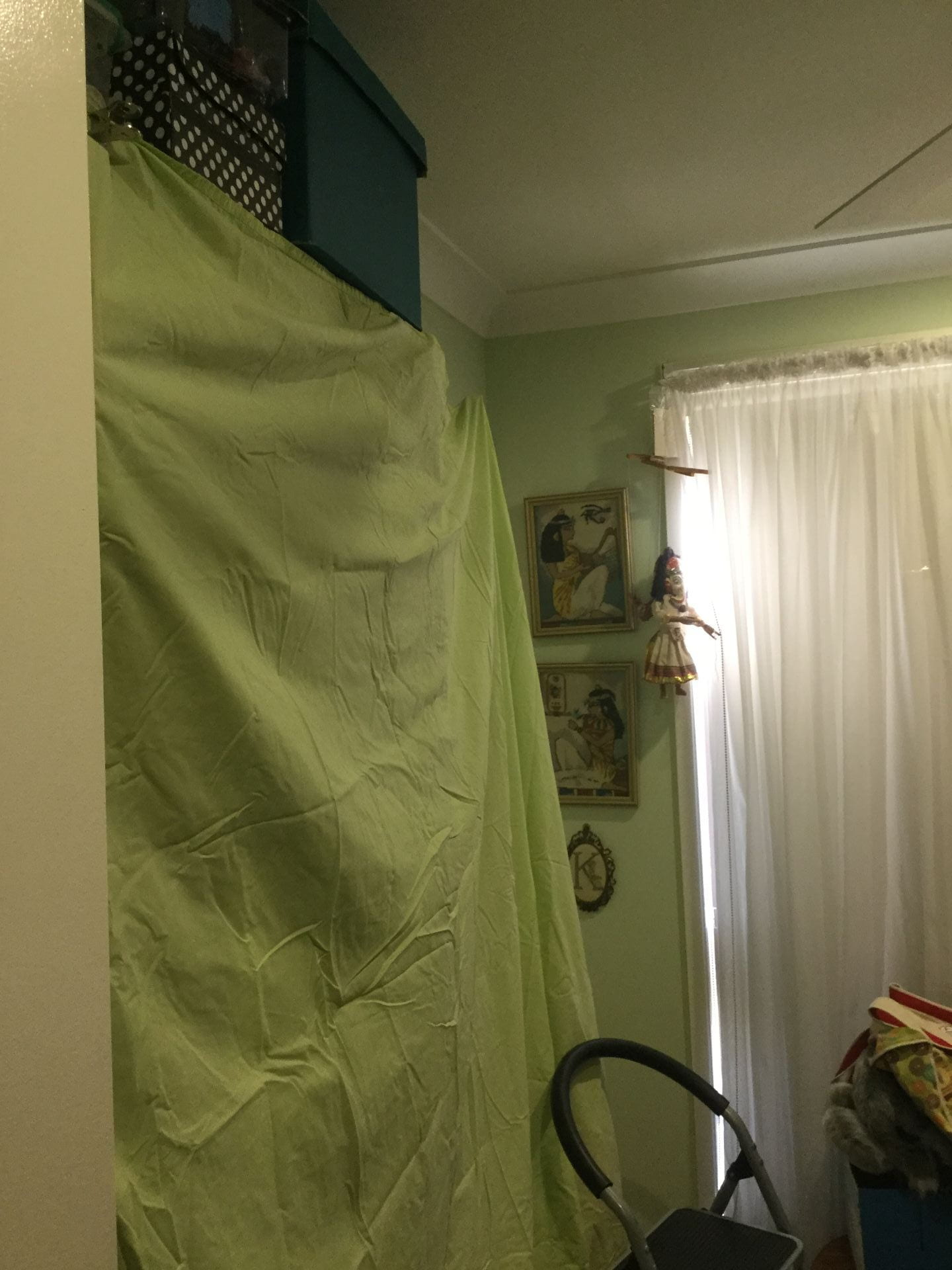 Green bedsheet covering the bookcase