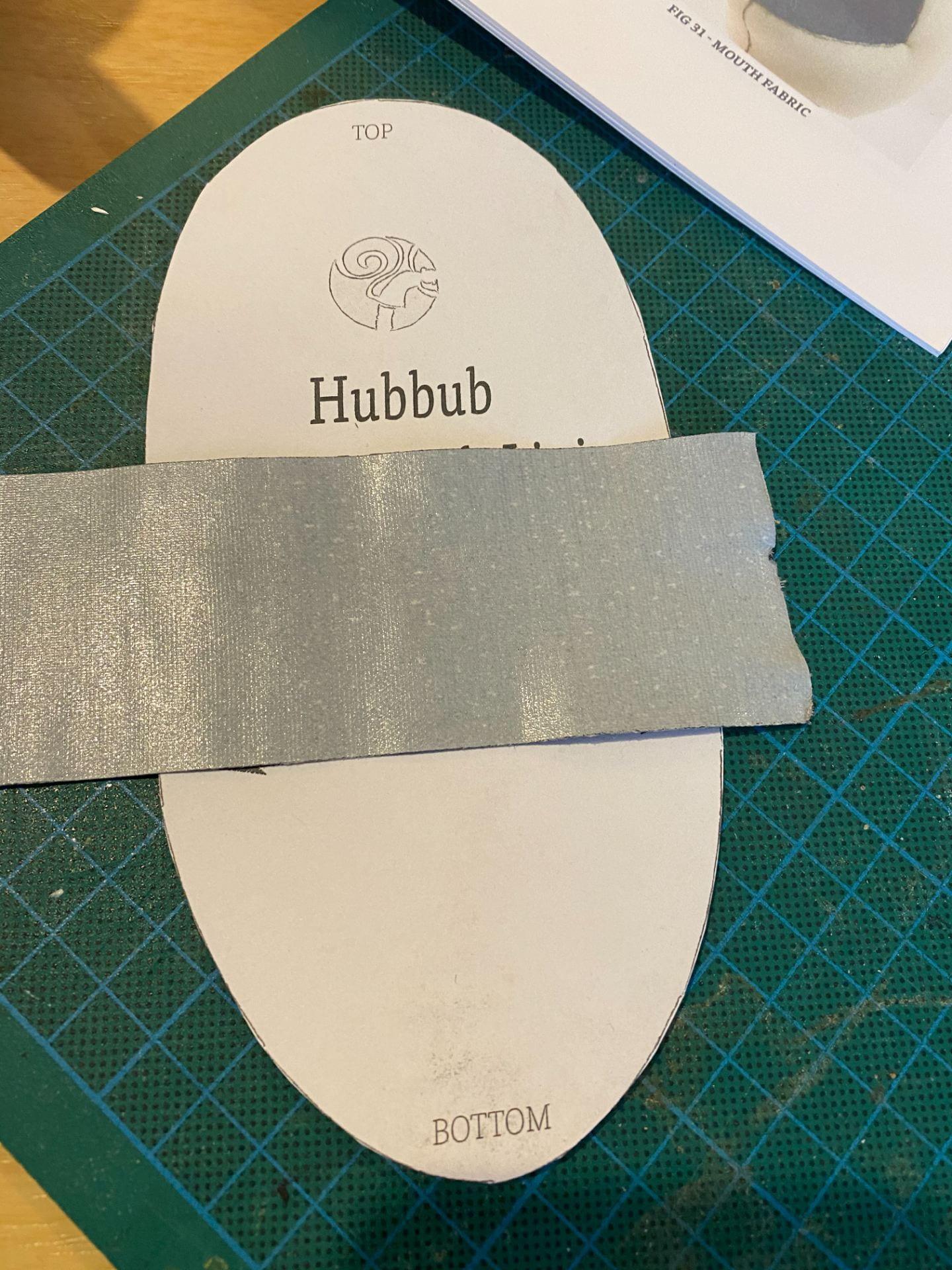 Gaffer tape sticky side up on top of a oval shaped pattern piece